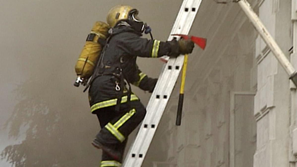 Palomies kiipeää palotikkaita pitkin.