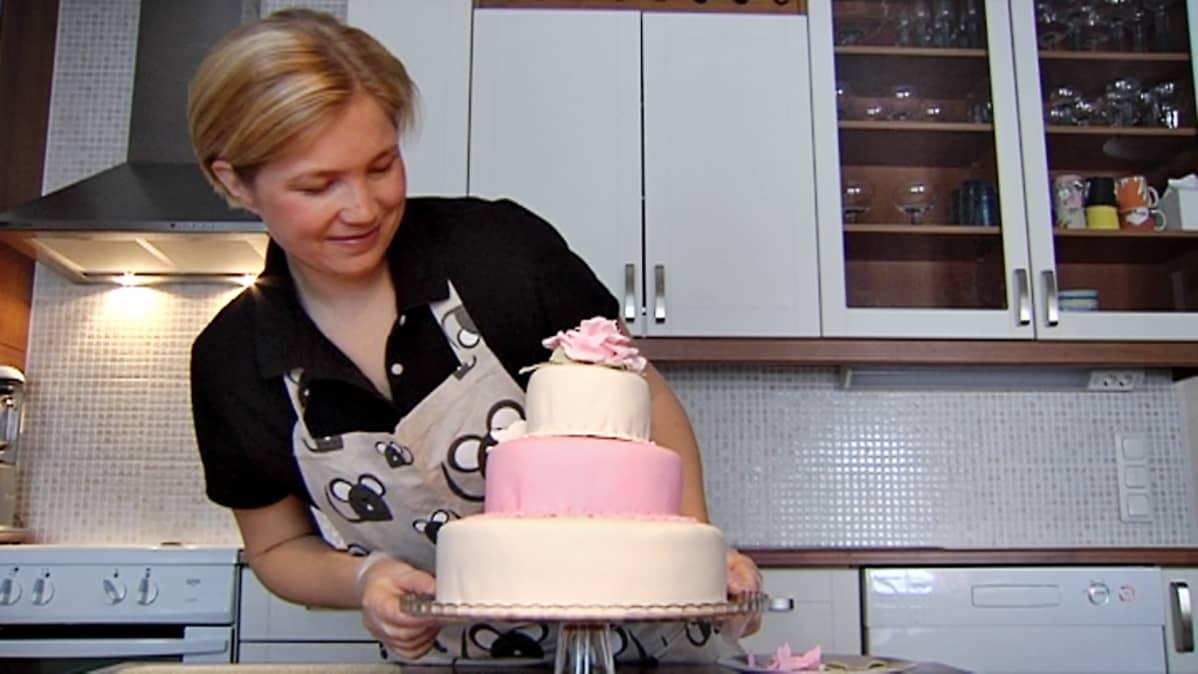 Taru Vihavainen katselee ihaillen kakkuansa.