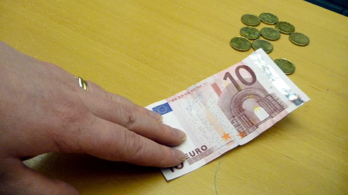 Kuvassa käsi pitää kympin seteliä pöydän päällä, jossa on muutamia pikkukolikoita.