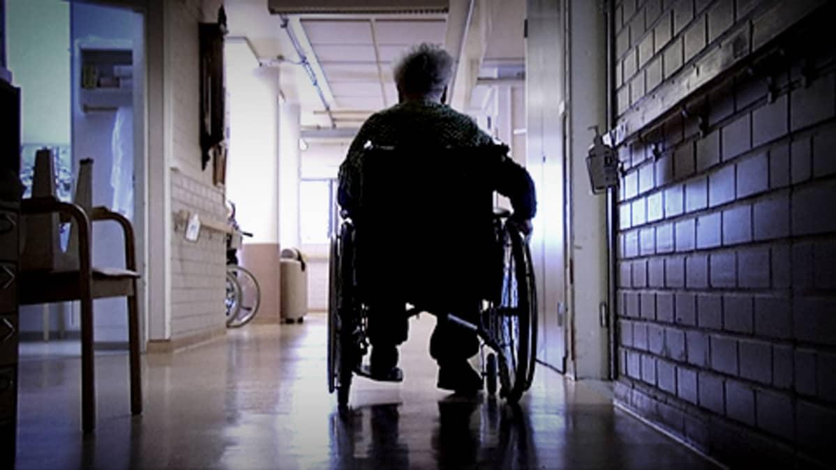 Vanhus istuu pyörätuolissa hoitolaitoksen käytävällä