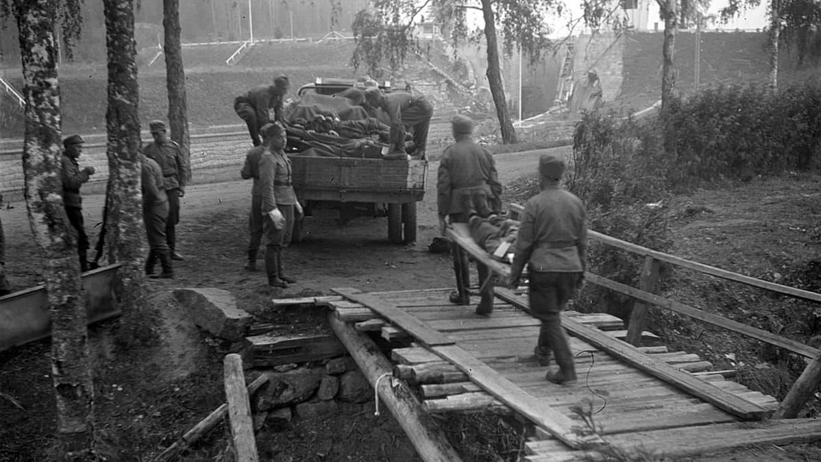 Kotiseutu on vallattu takaisin: suomalaiset ovat Rättijärvellä elokuussa 1941. Taustalla on vaurioitunut kanava ja sulku.
