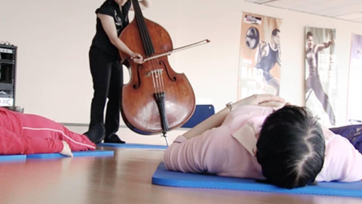 Ihmiset makaavat lattialla ja kuuntelevat kontrabasson soittoa.