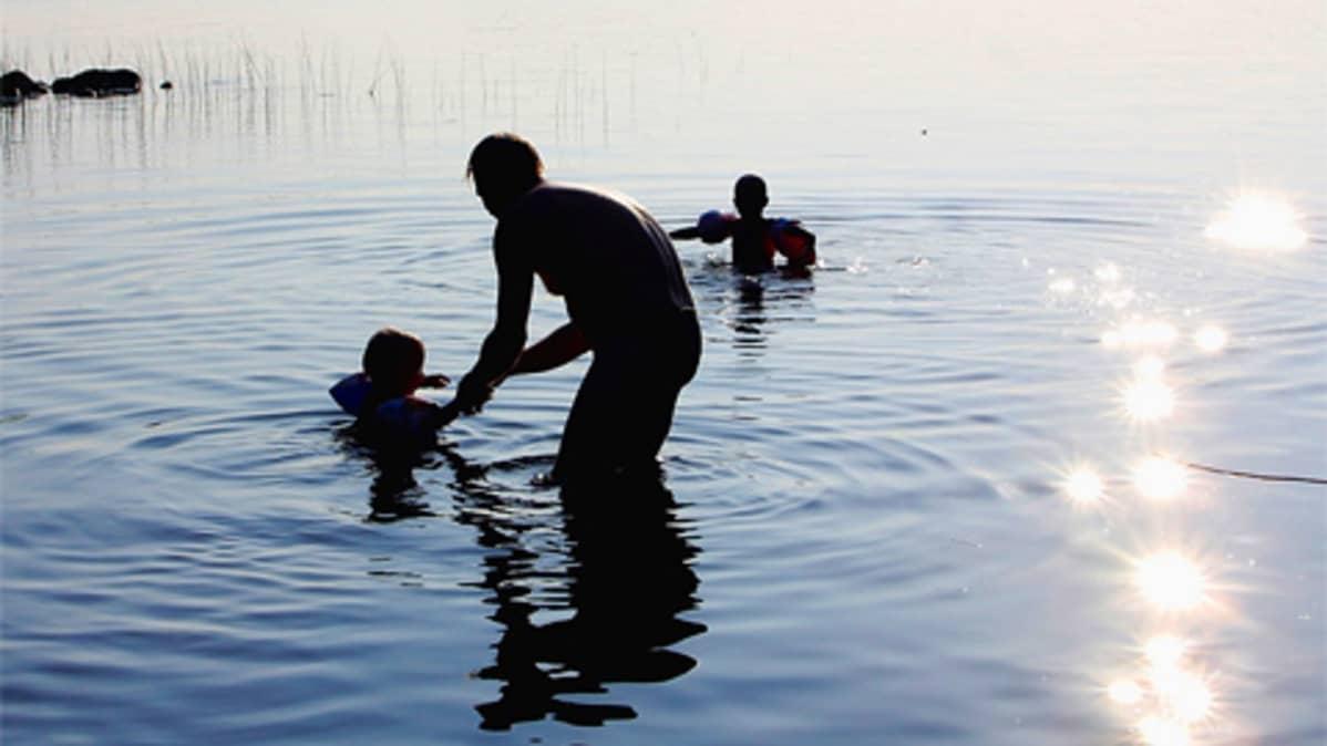 Isä ja lapset rantavedessä