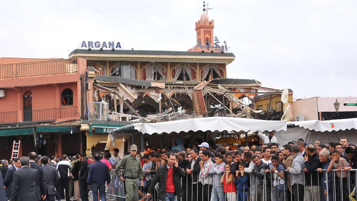 Argana-kahvila vaurioutui pahoin räjähdyksessä 28. huhtikuuta 2011. Kahvilan ulkopuolella tungeksii ihmisiä. Viranomaiset ovat aidanneet alueen uteliaiden pitämiseksi loitolla rikospaikalta.