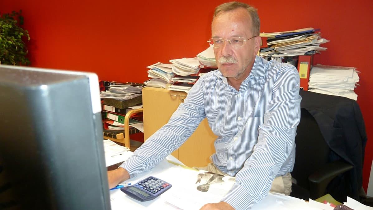 Porin palveluliikelaitoksen johtaja Kaj Kainulainen istuu työpöytänsä ääressä.