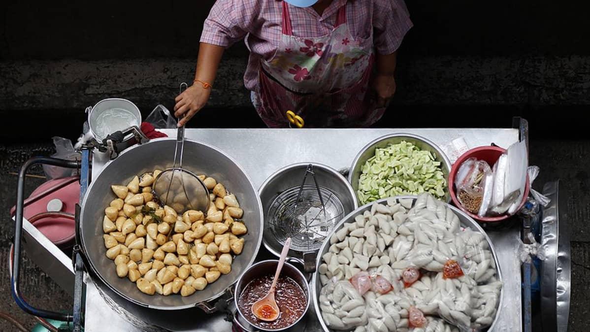 Thaimaalainen katukeittiön pitäjä valmistaa annoksia.