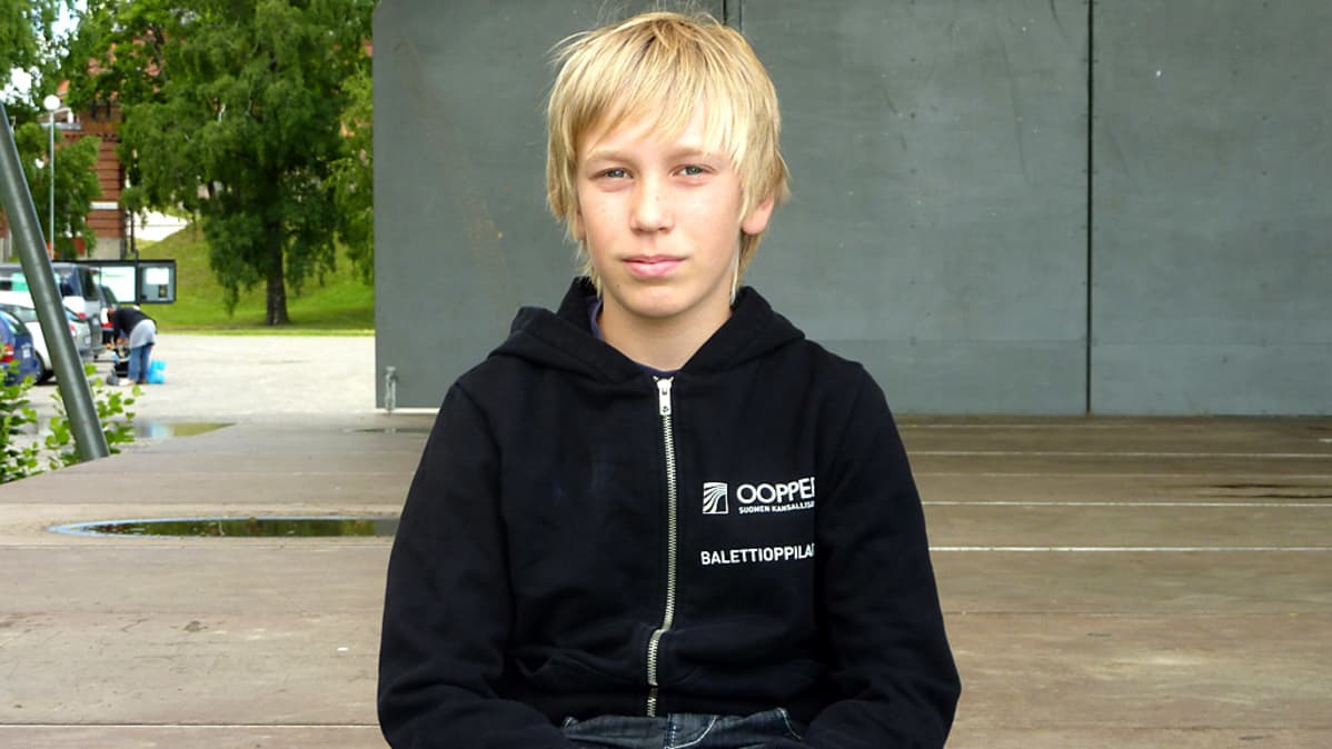 poika istuu esiintymislavan reunalla
