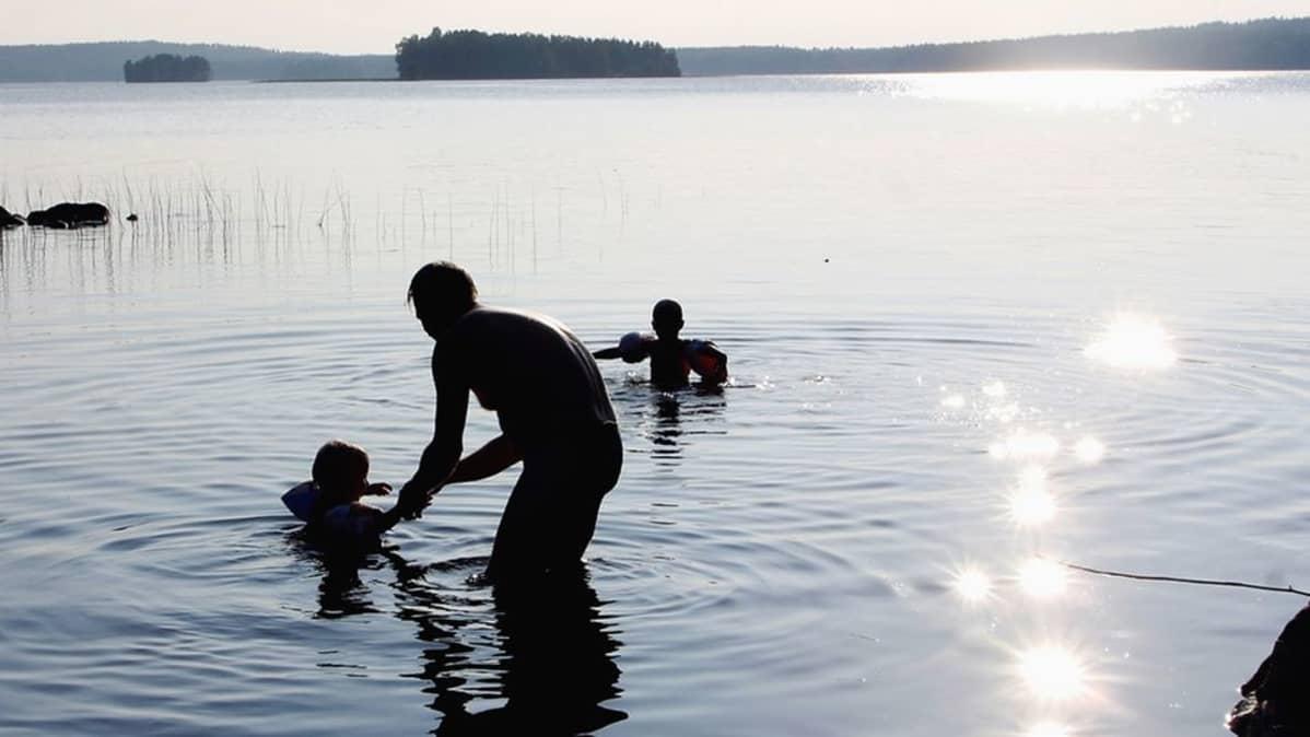 Mies uimassa kahden lapsen kanssa järvessä.