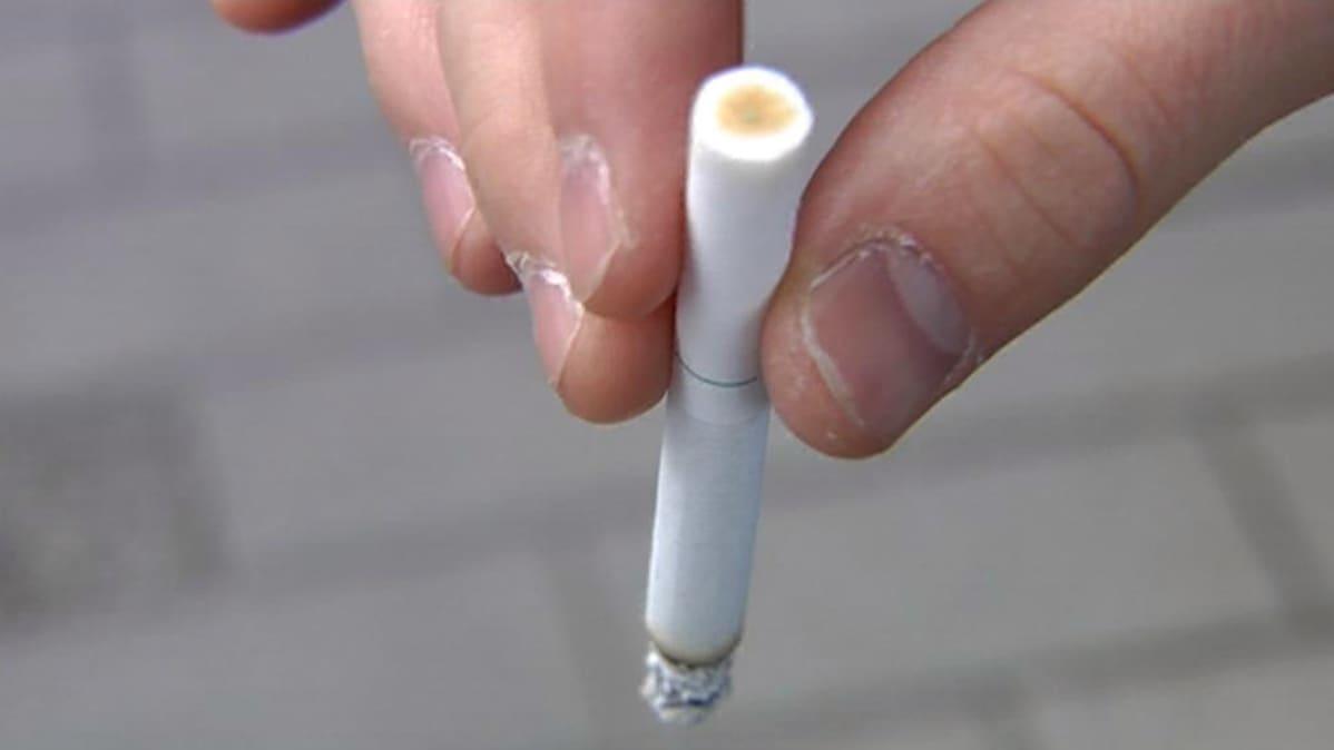Tupakka tupakoitsijan sormissa.