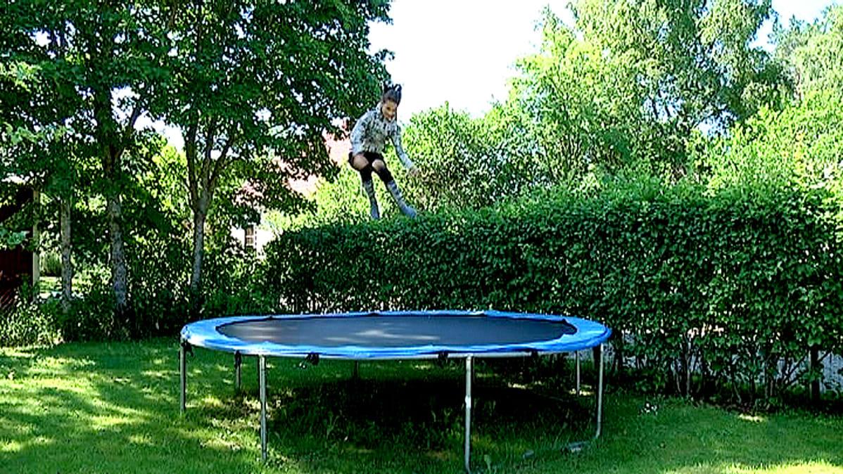 Tyttö hyppii trampoliinilla