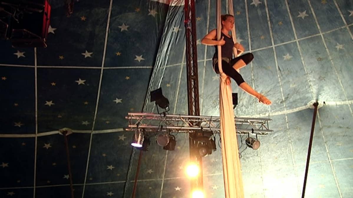 Nainen voimistelee sirkusteltan katosta roikkuvassa kankaassa.