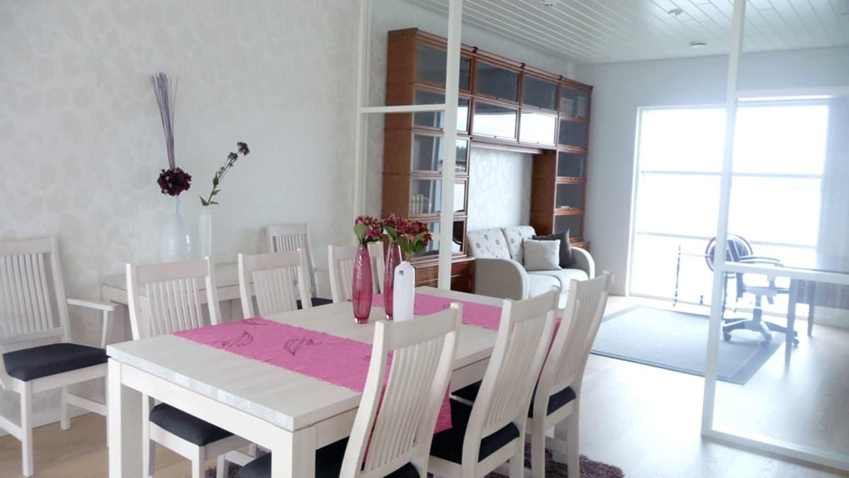 Kuvassa ruokapöytä ja tuoleja, pöydällä kaksi pöytäliinaa ja maljakoita