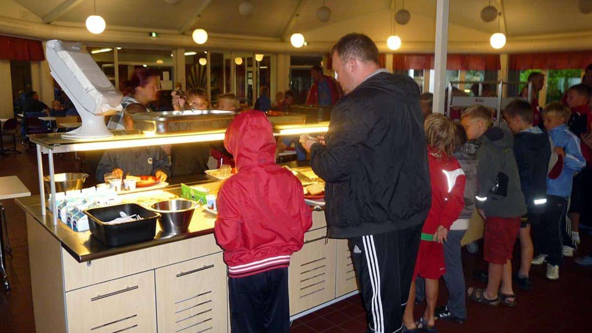 Valmentaja ja lapset ottavat ruokaa.