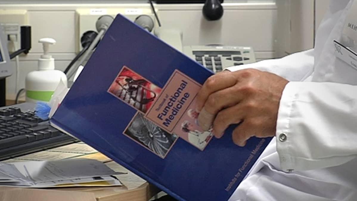 Lääkäri selaa kirjaa.
