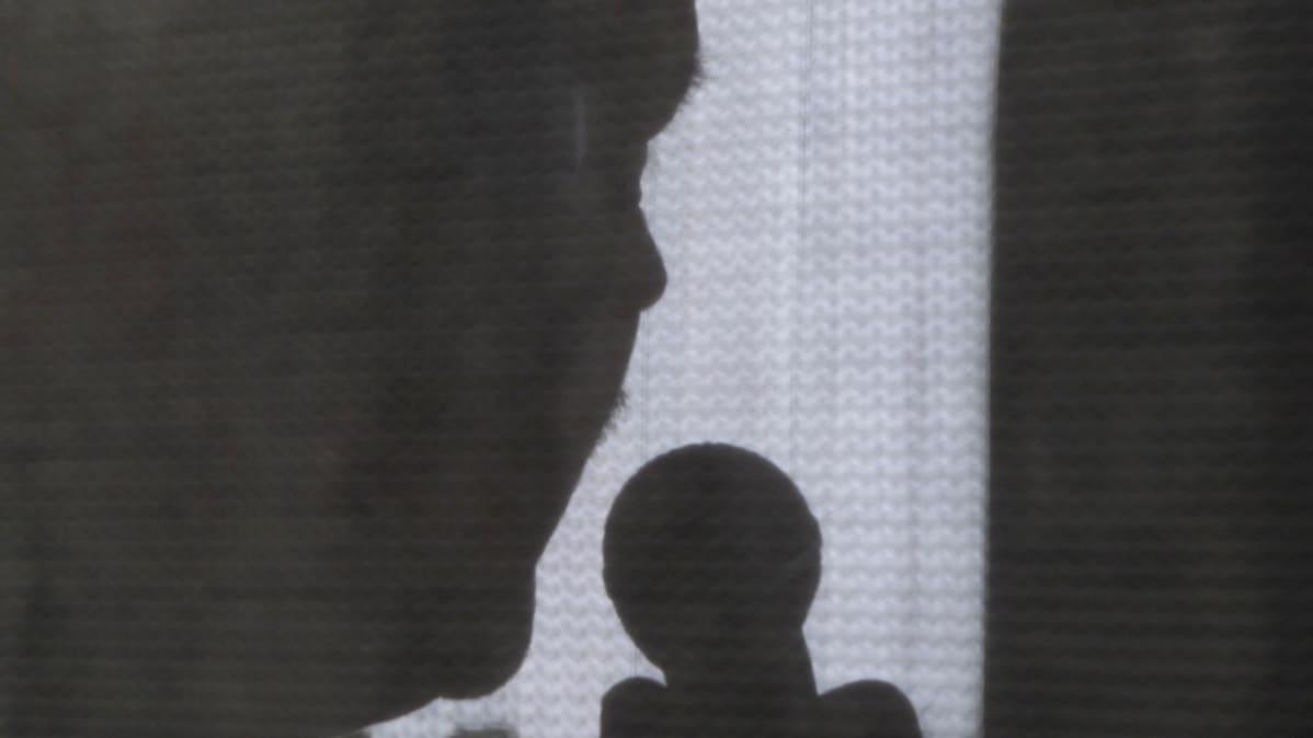 Kuvassa mieslaulaja ja mikrofoni heijastuu tummana varjona kirkasta valoa vasten.