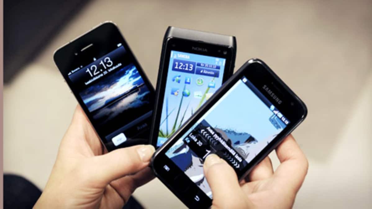 Älypuhelimet iPhone, Nokia ja Samsung viuhkana kädessä.