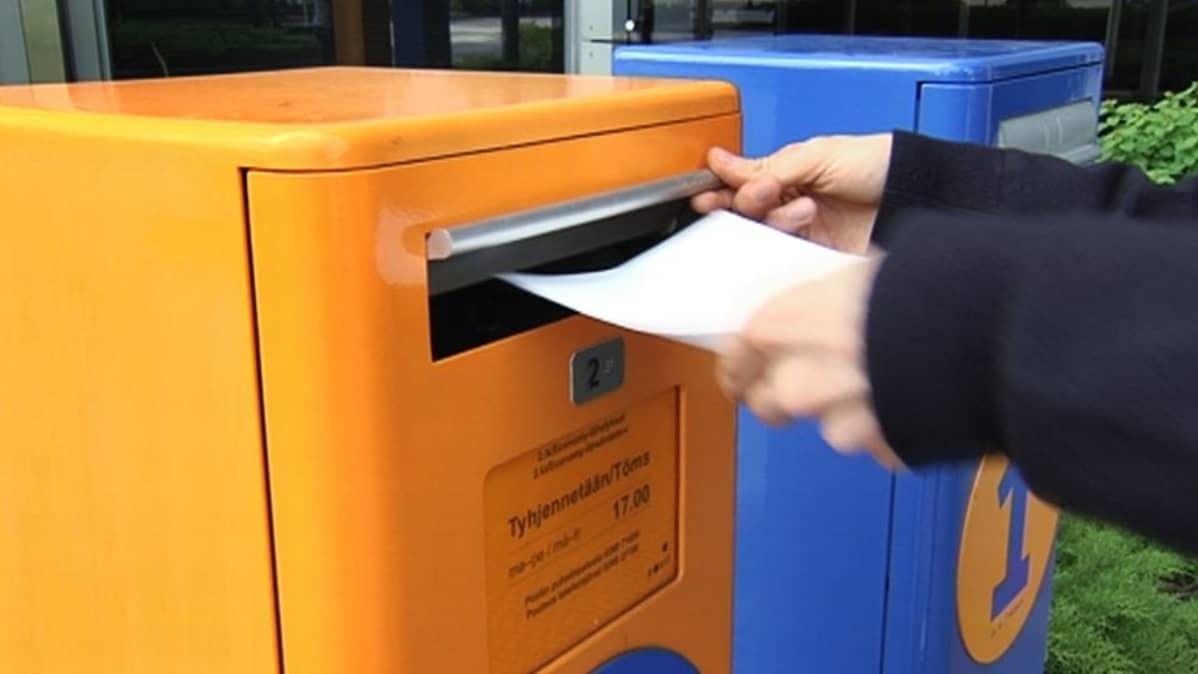 Kirjekuorta laitetaan postilaatikkoon.
