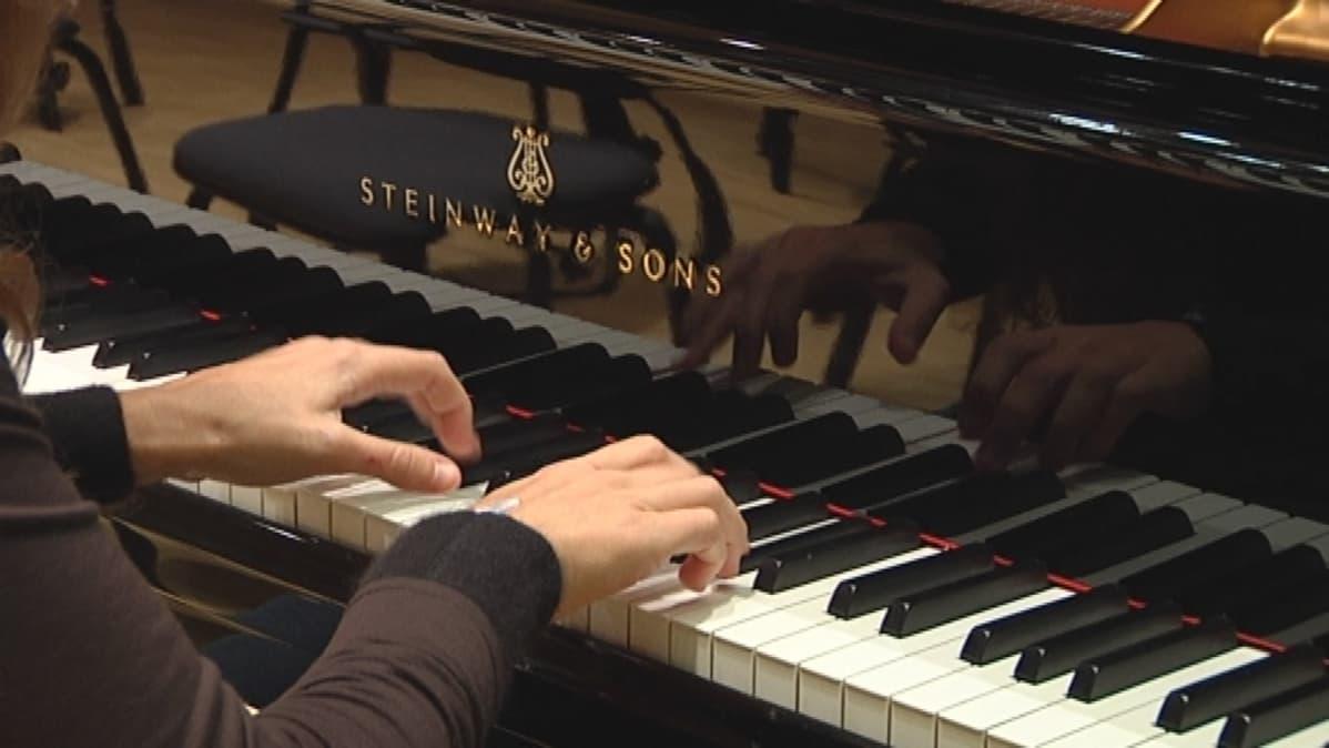 Steinway -flyygelin koskettimet ja pianistin kädet.