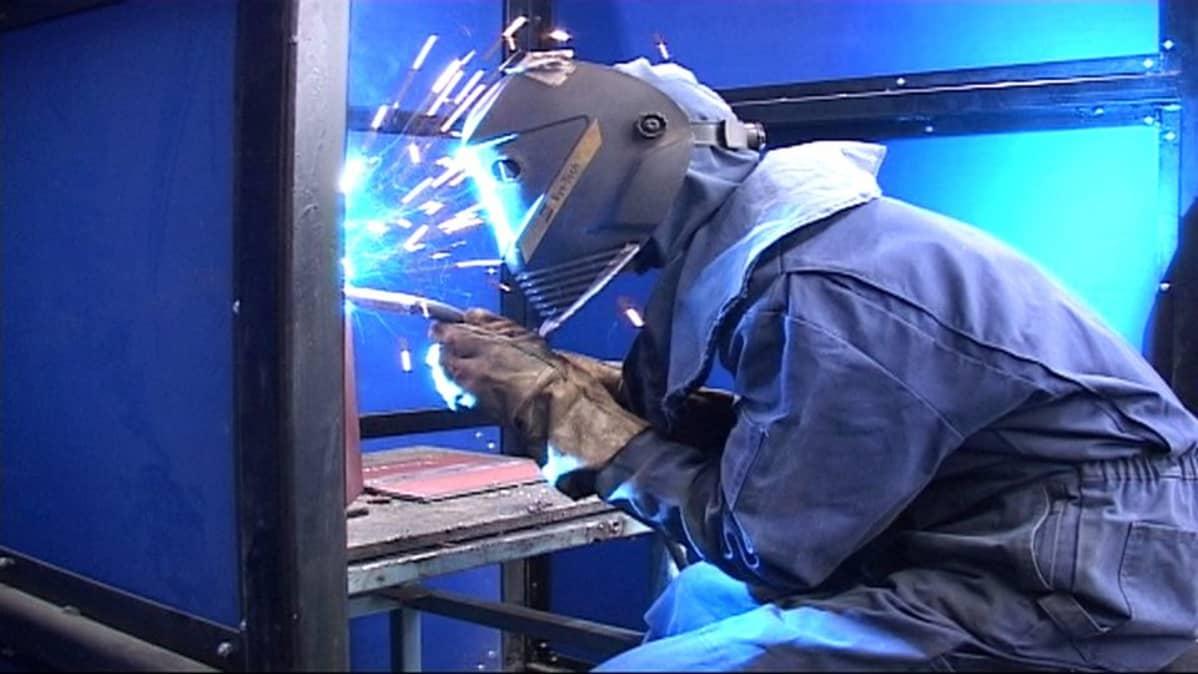 Opiskelija hitsaa palkkia sinisten sermien sisällä.