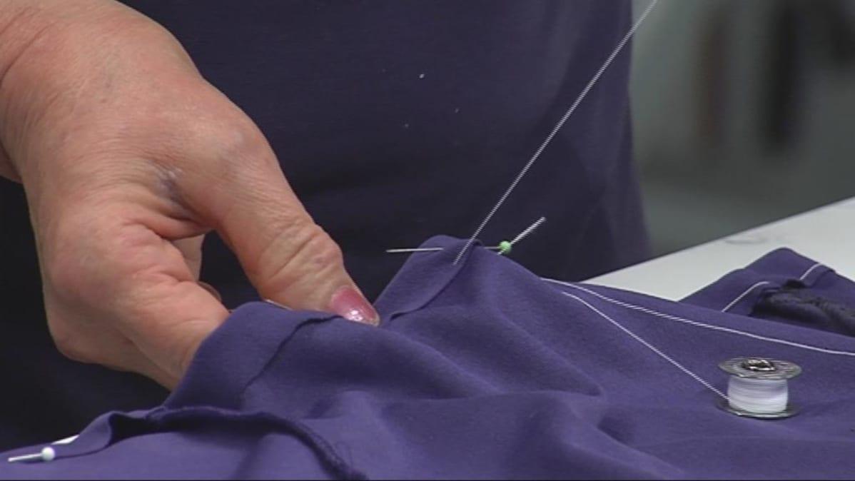 Nainen harsii keskeneräistä paidanhelmaa.
