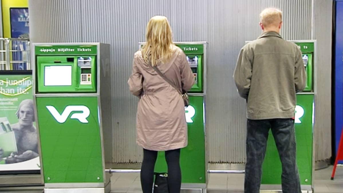 Mies ja nainen ostavat junalippuja automaateista rautatieasemalla.