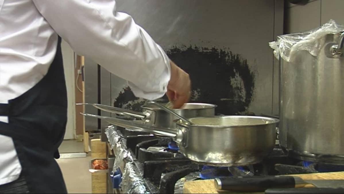 Kokki valmistaa ruokaa ravintolan keittiössä.