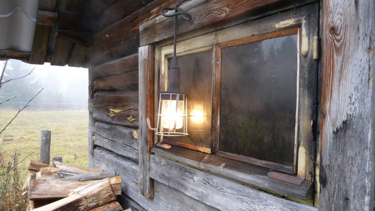 Savu leijailee savusaunan ikkunankarmeista.