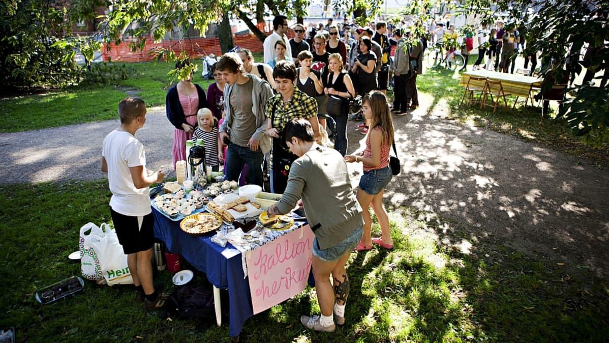 Ihmiset jonottivat vegaanisia leivonnaisia tarjoilleelle Kallion Herkut -myyntipöydälle Karhupuistossa Helsingissä toisena Ravintolapäivänä 21.8.2011.