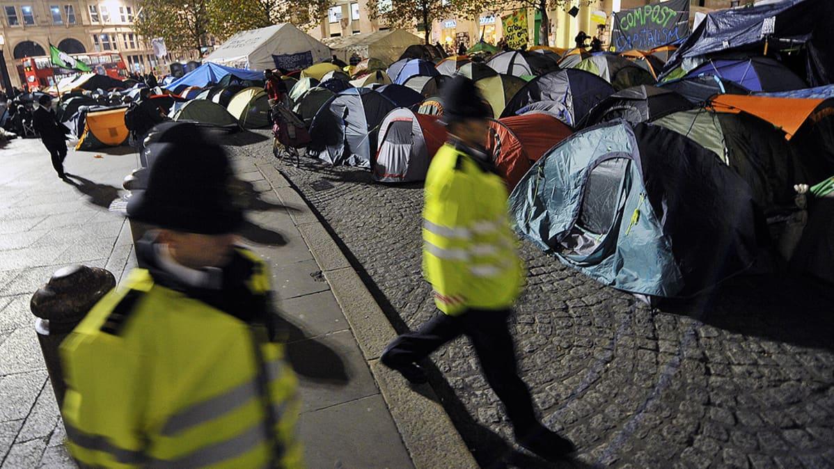 Poliisit kävelevät St. Paulin katedraalin edustalla sijaitsevan  mielenosoittajien telttaleirin ohitse.