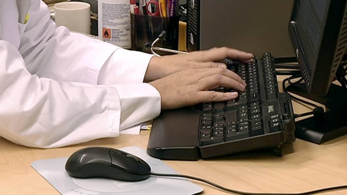 Lääkäri syöttää tietokoneelle potilaan tietoja järjestelmään.