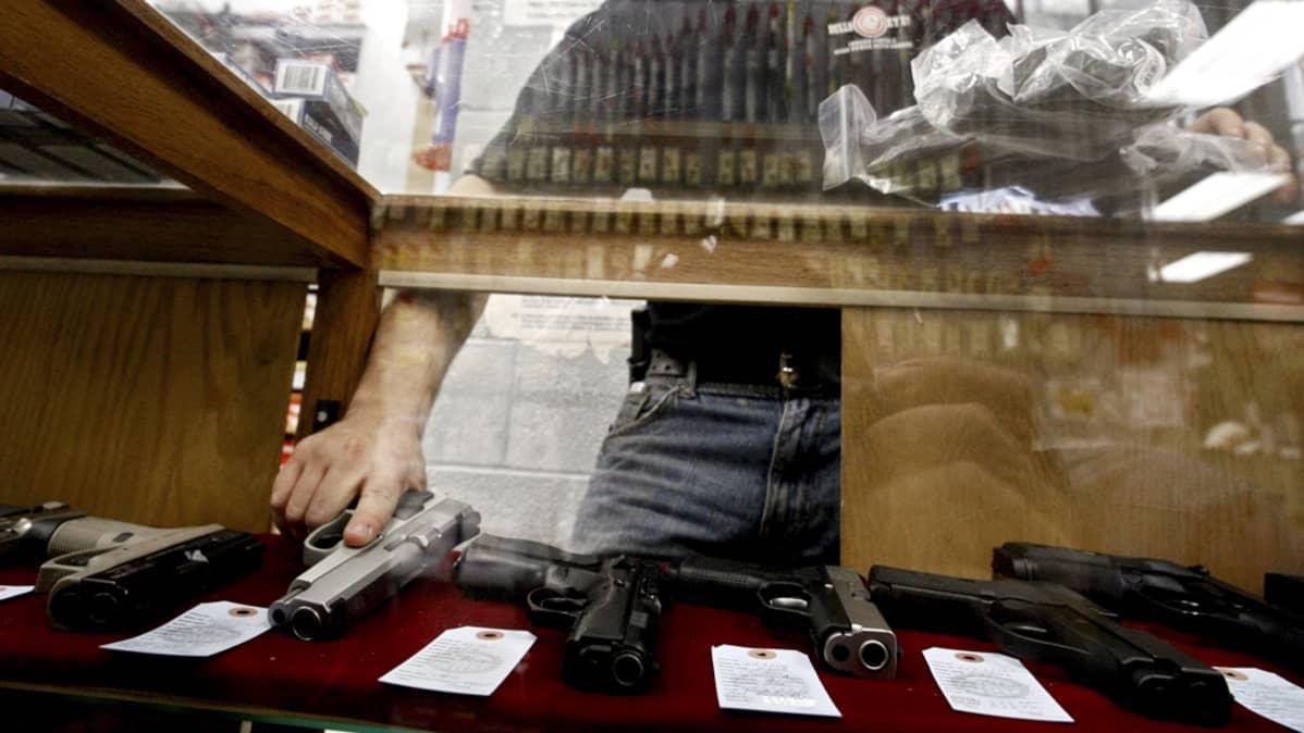 Työntekijä palvelee asiakasta ojentamalla tälle aseen Wichitassa, Kansasissa, 26. kesäkuuta 2008.