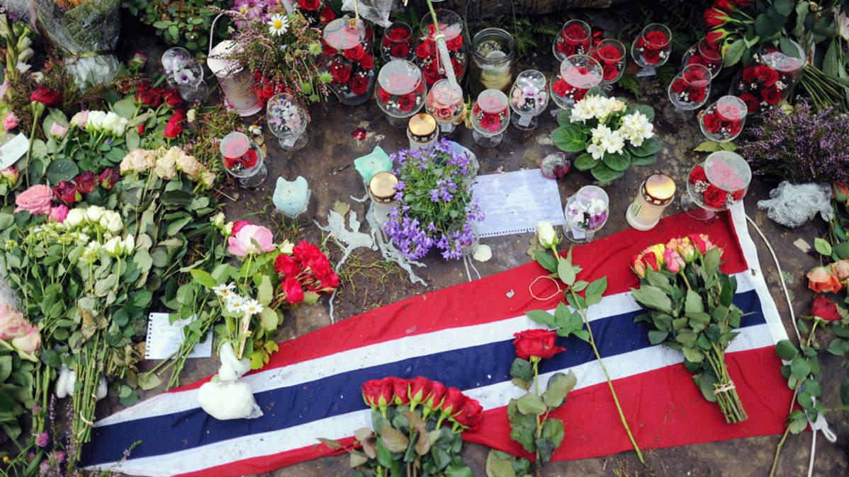 Kukkia ja kynttilöitä Norjan viirin päällä.