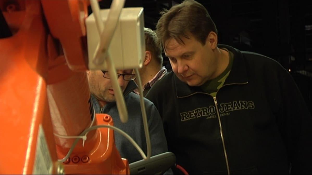Kuvassa Jari Kantoniemi tutkii robottia