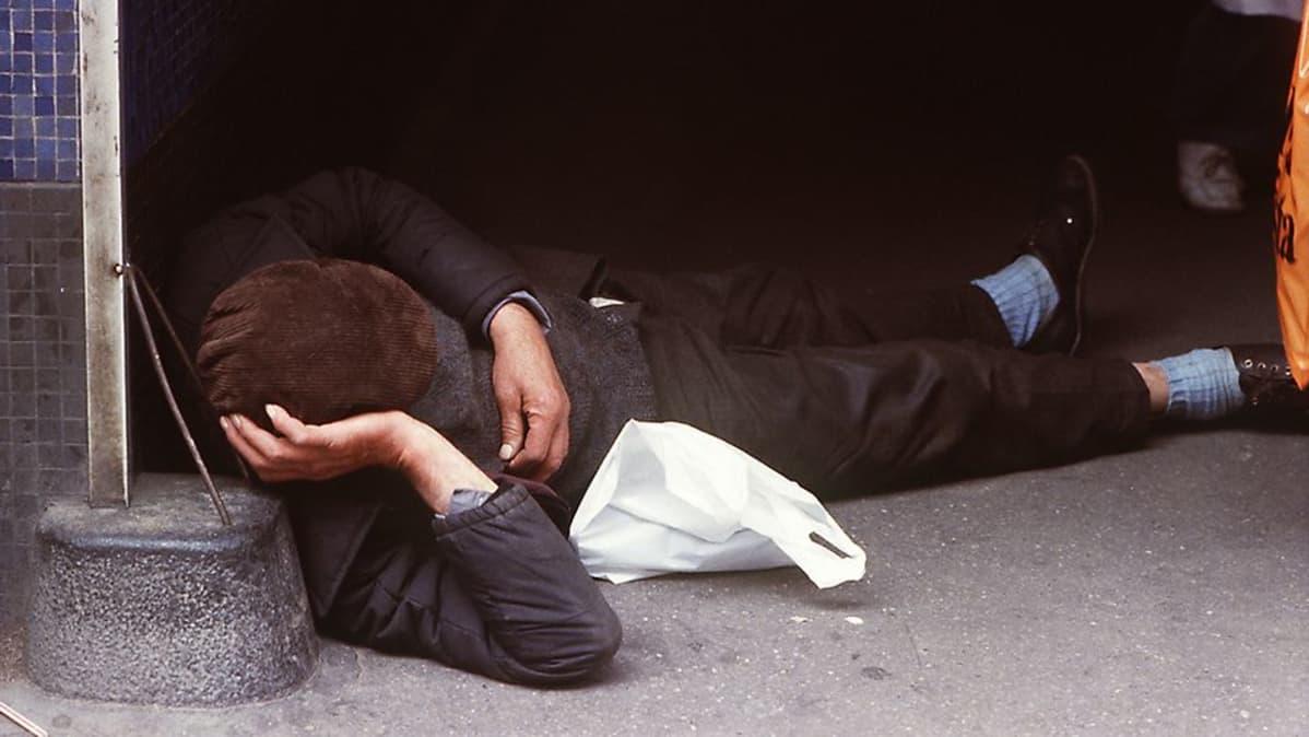 Alkoholisti nukkuu kassinsa vieressä jalkakäytävällä.