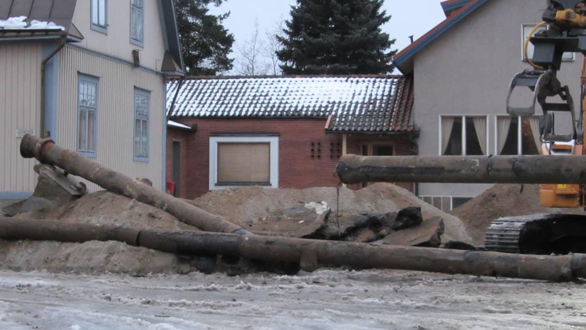 Kuvassa vanhoja vesijohtoputkia, taloja ja kaivinkone