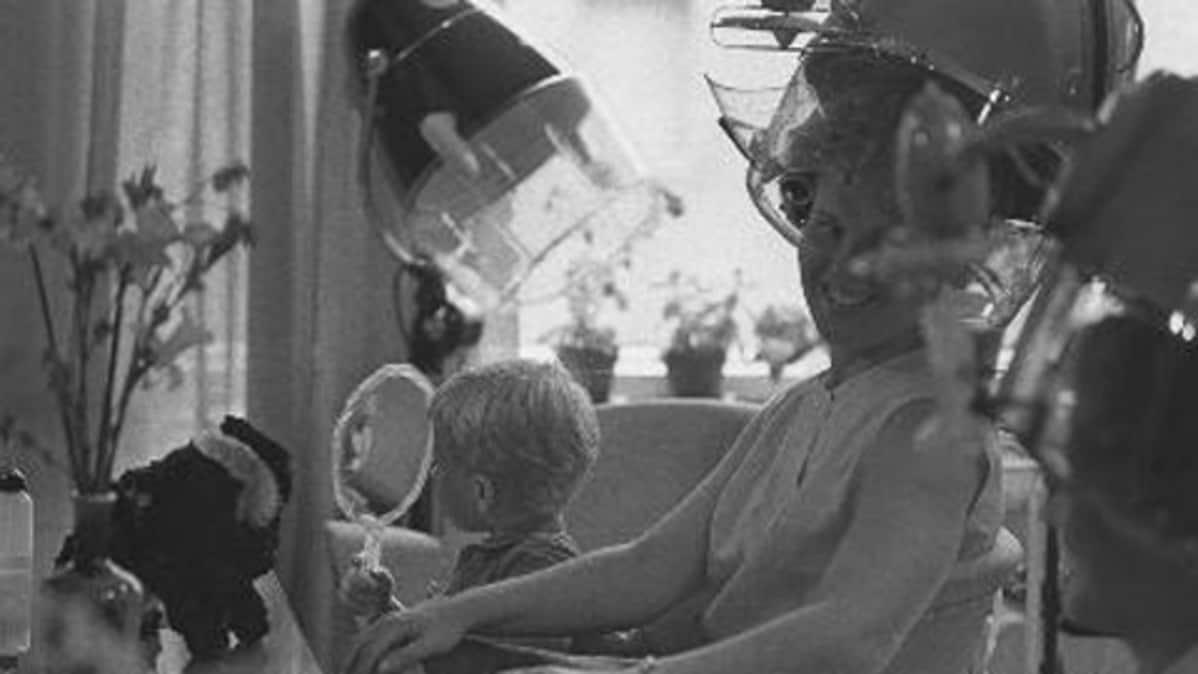 Kampaamo Tampereella 60-luvulla. Naisasiakas hiustenkuivaajassa, pieni poika peilaa vieressä