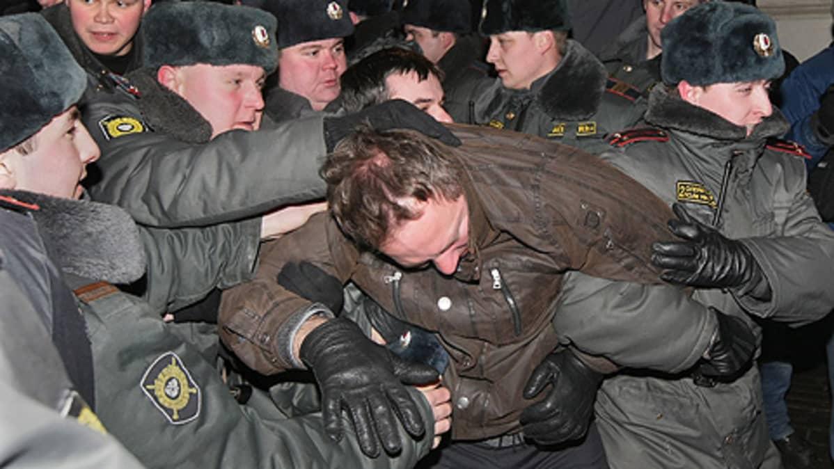 Useita poliiseja pitää kiinni mielenosoittajaa.
