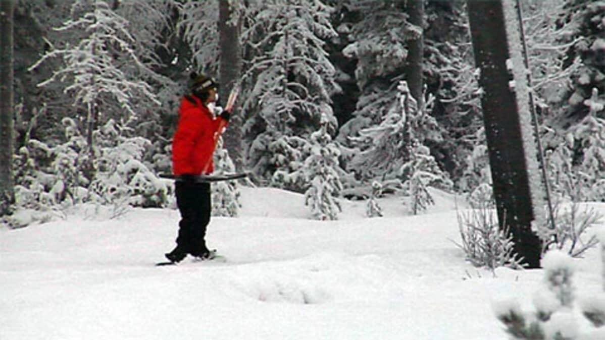 Lumilautailija matkaa hissillä Iso-Syötteellä.