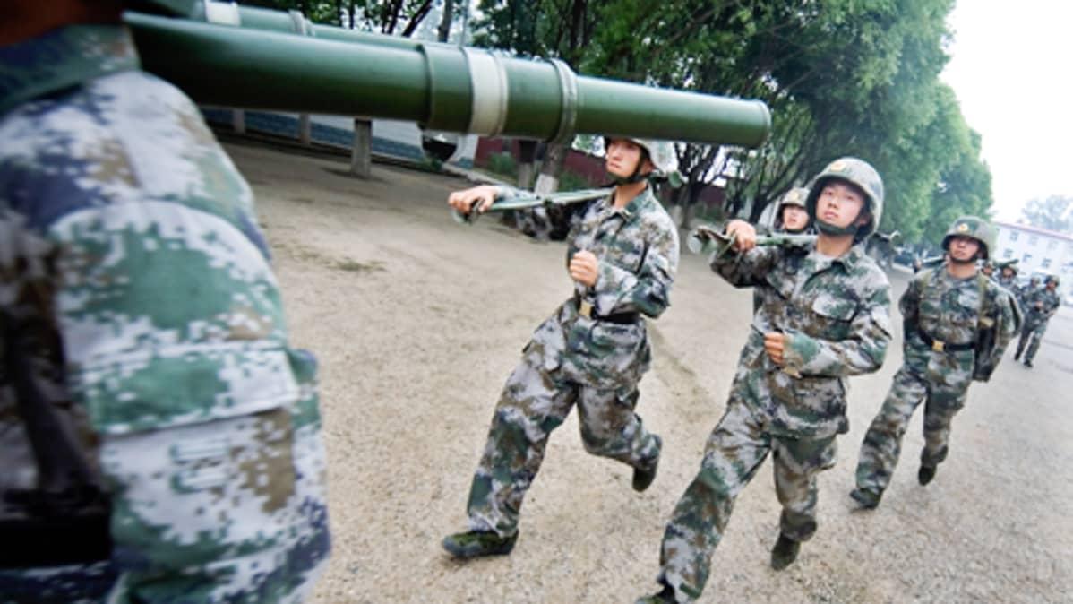 Kiinalaiset sotilaat juoksevat aseet olillaan Pekingissä.