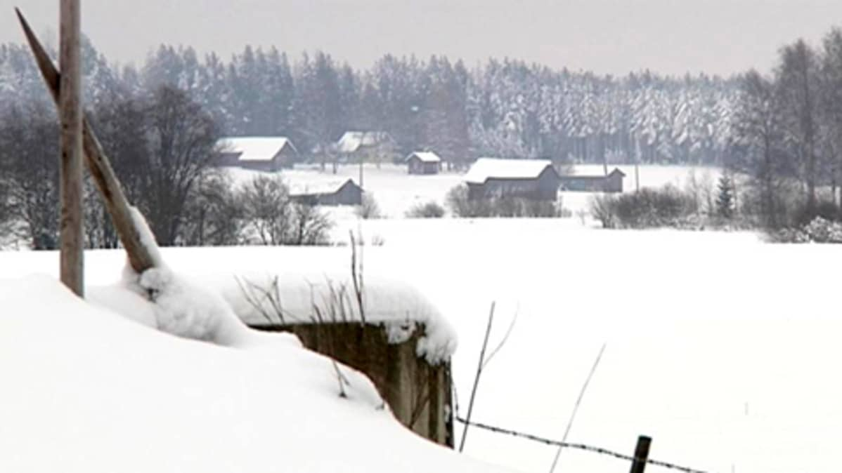 Latoja ja muita rakennuksia pellon takana metsän laidassa.