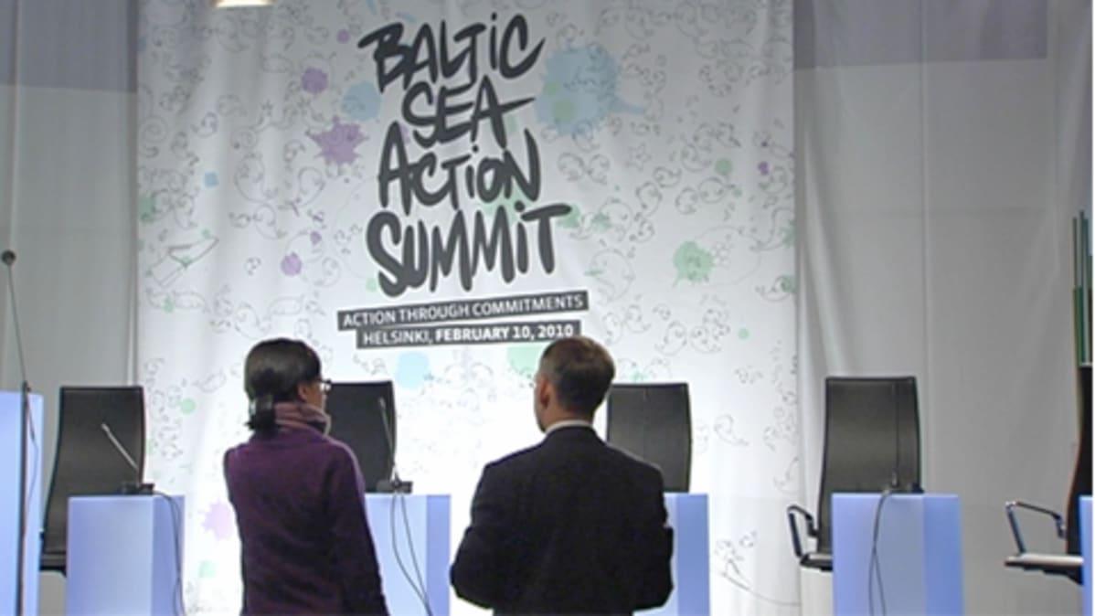 Kokouksen järjestelijät keskustelevat esiintymislavan edustalla.Lavalla näkyy esiintyjien tuoleja ja Baltic Sea Action Summit lakana