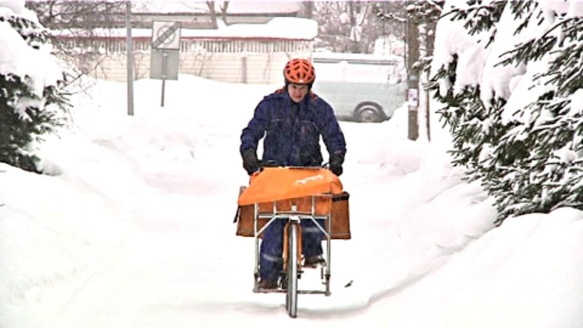 Postinjakaja Vesa Naskali pyöräilee lumisella tiellä.