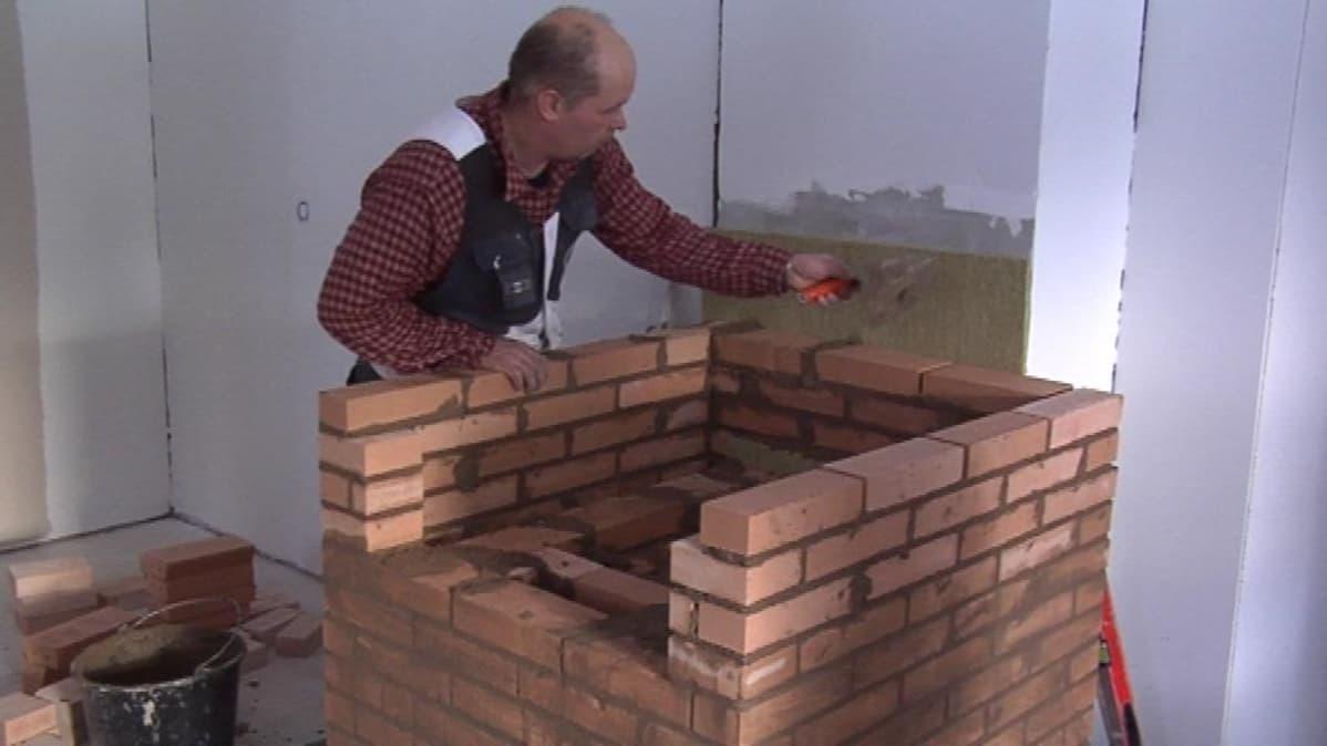 Raimo Halonen muuraa.