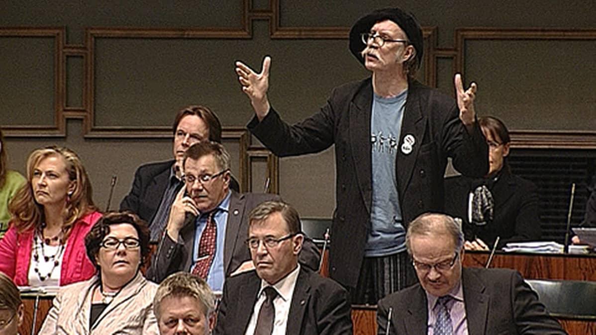 Pertti Virtanen puhuu eduskuntasalissa. Levittelee käsiään.