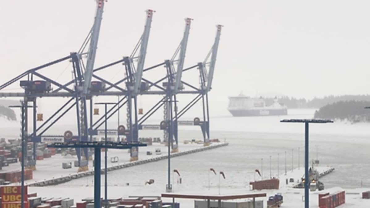 Finnlinesin laiva etääntyy satamasta. Sataman kaikki isot nosturit ovat ylhäällä. Satama-alueella ei näy ihmisiä eikä autoja.