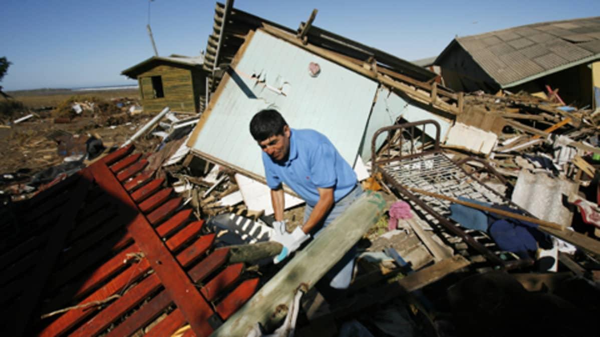 Mies etsii tavaroita romahtaneen talon raunioissa Chilessä.