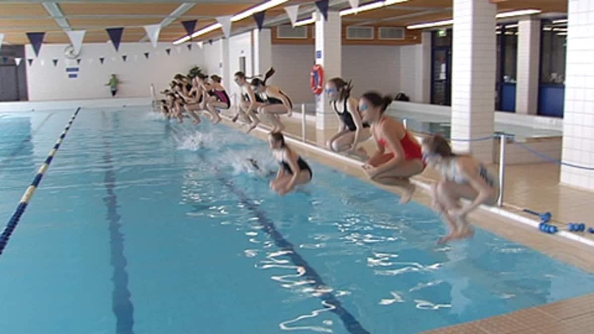 Koululaiset hyppäävät rivissä uima-altaaseen.
