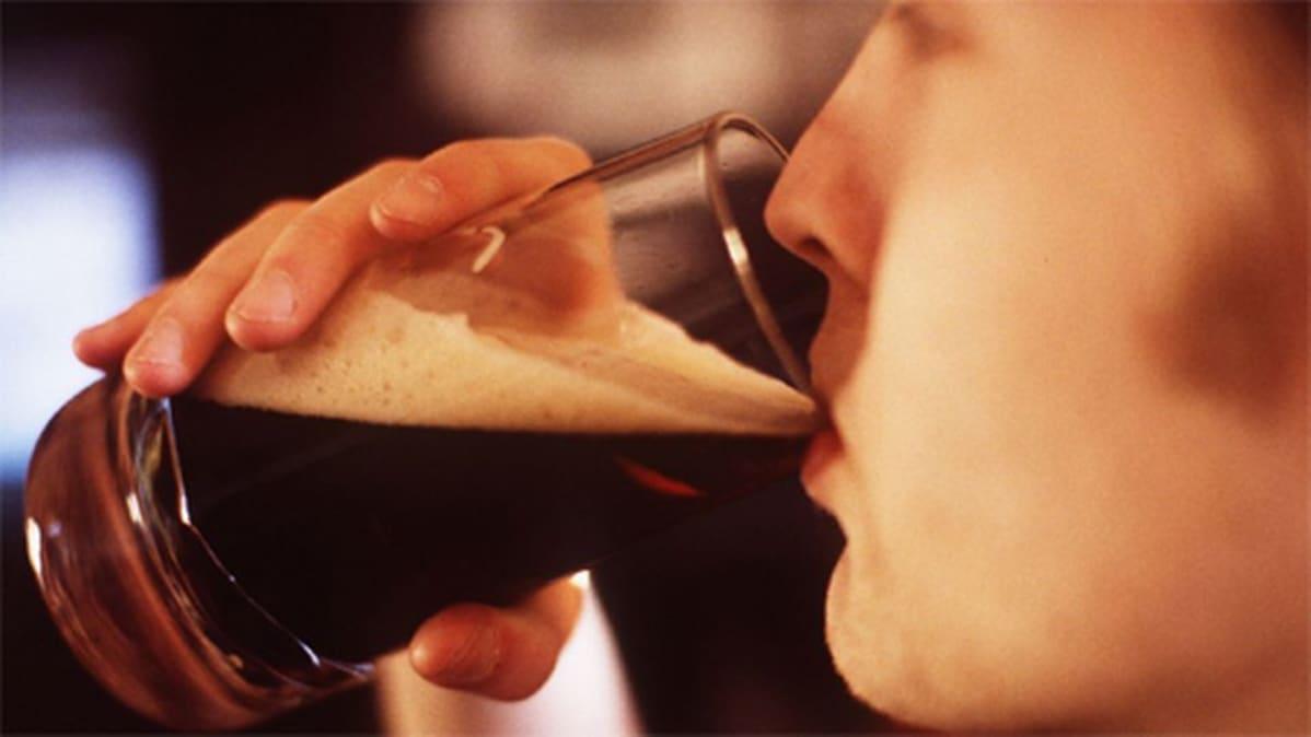 Nuori mies juo tummaa olutta lasista.