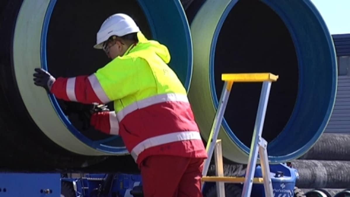 Mies tutkimassa kaasuputkea