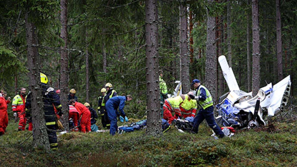 Pudonnut kone ja pelastushenkilöstöä metsässä
